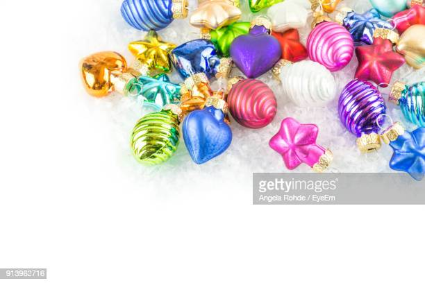 close-up of multi colored christmas ornaments over white background - angela rohde stock-fotos und bilder