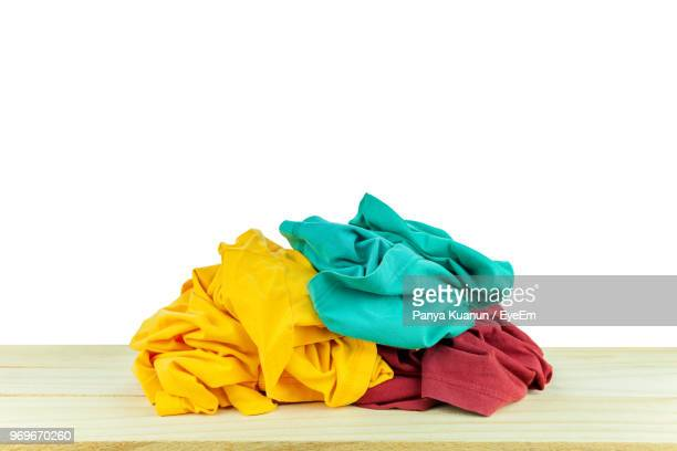 close-up of multi colored clothes on table against white background - heap stock pictures, royalty-free photos & images