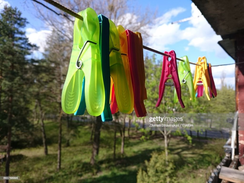 Closeup Of Multi Colored Clothespins Hanging On Rope Against Trees ...