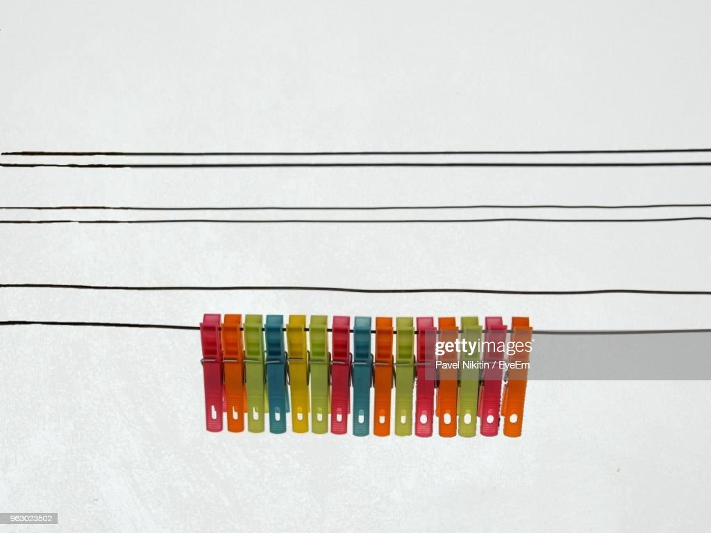 Closeup Of Multi Colored Clothespins Hanging On Wire Against Clear