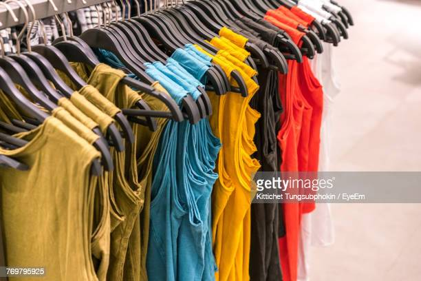 close-up of multi colored clothing hanging in row - clothes rack stock pictures, royalty-free photos & images