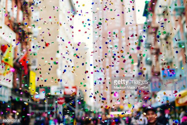 close-up of multi colored confetti in city - stadtviertel stock-fotos und bilder