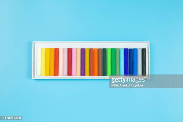 close-up of multi colored crayons in box over blue background - クレヨン ストックフォトと画像