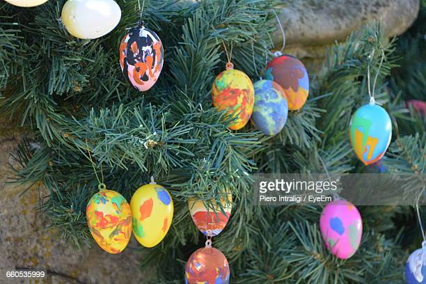 close-up of multi colored decorated eggs hanging on christmas tree - easter mask stock pictures, royalty-free photos & images