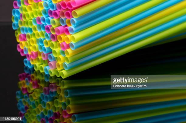 close-up of multi colored drinking straws on black background - 束 ストックフォトと画像