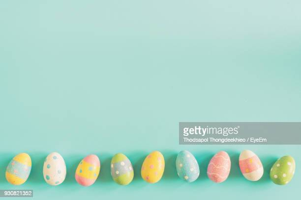 close-up of multi colored easter eggs against wall - easter egg stock pictures, royalty-free photos & images