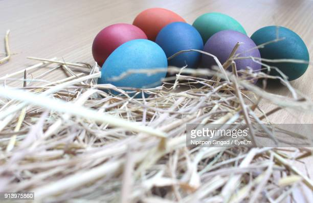 Close-Up Of Multi Colored Easter Eggs And Hay On Table