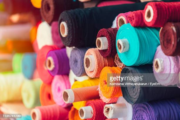 close-up of multi colored fabric rolls for sale at market - rolled up stock pictures, royalty-free photos & images