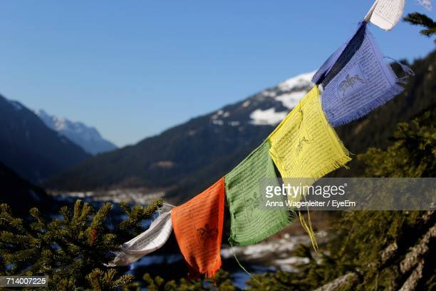 Close-Up Of Multi Colored Flags Hanging On Mountain Against Sky