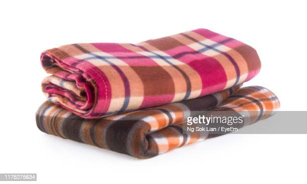 close-up of multi colored folded blankets over white background - blanket stock pictures, royalty-free photos & images