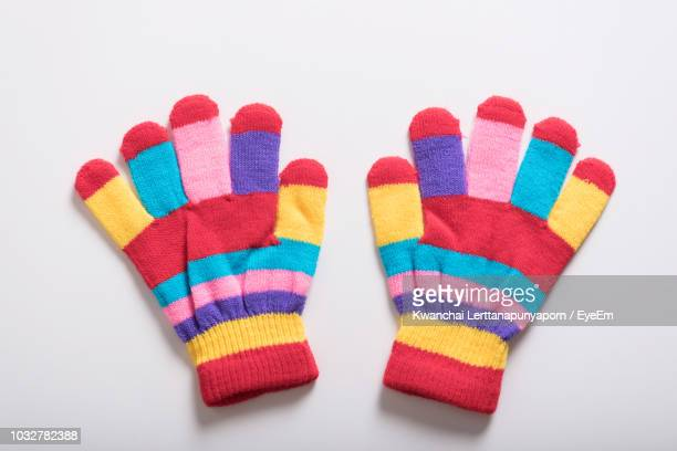 Close-Up Of Multi Colored Gloves Over White Background