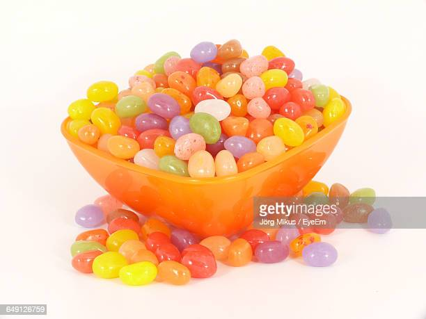 Close-Up Of Multi Colored Jellybeans In Bowl Against White Background