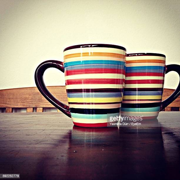 Close-Up Of Multi Colored Mugs On Table At Home