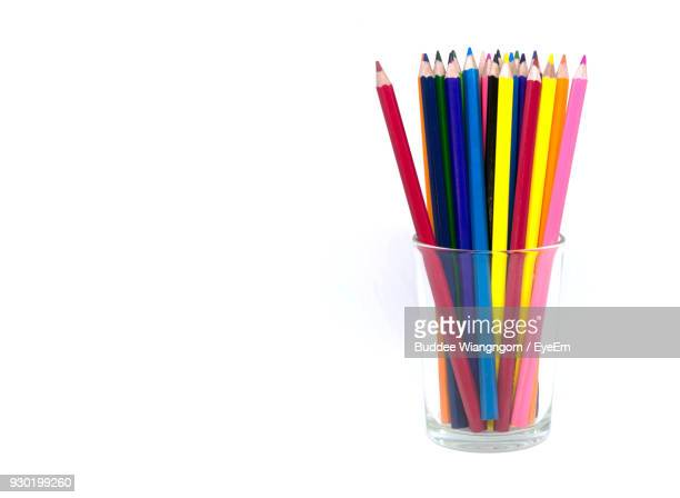 Close-Up Of Multi Colored Pencils In Glass Container Over White Background