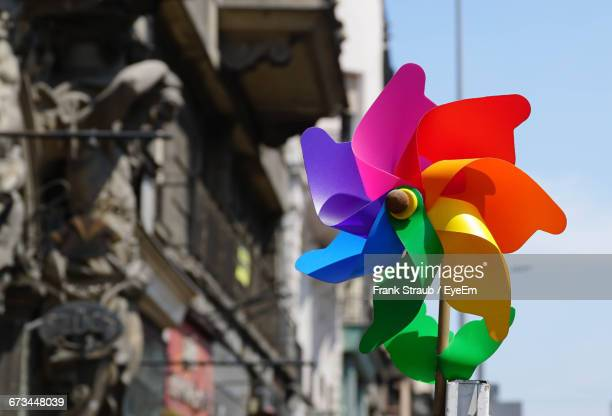 close-up of multi colored pinwheel against old building - paper windmill stock photos and pictures