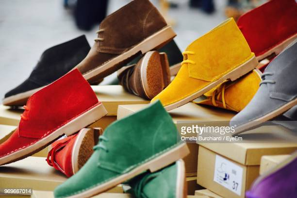 close-up of multi colored shoes on boxes at shop for sale - multi coloured shoe stock pictures, royalty-free photos & images