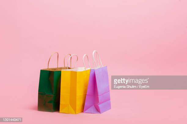 close-up of multi colored shopping bags over pink background - 買い物袋 ストックフォトと画像