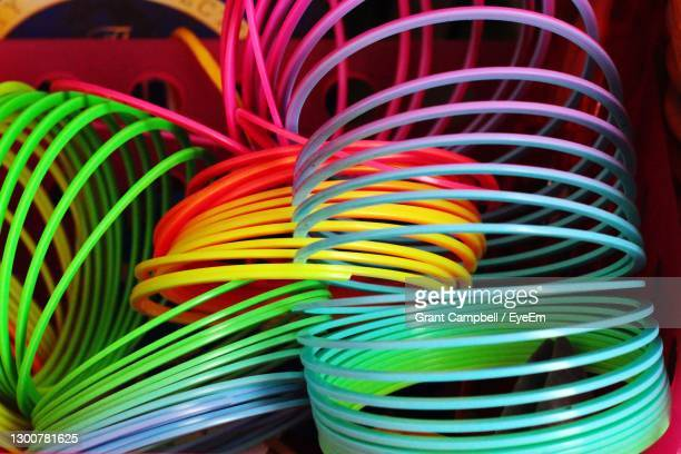 close-up of multi colored slinky - green colour stock pictures, royalty-free photos & images