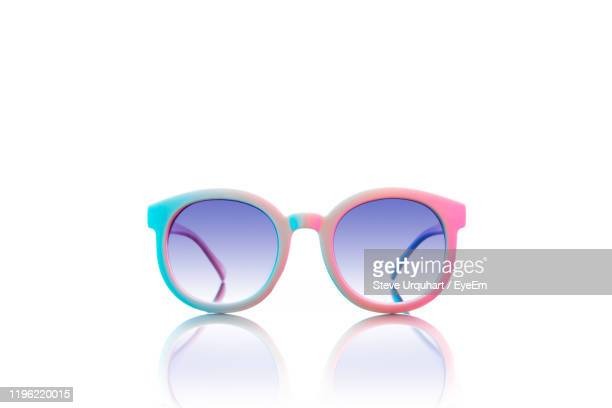 close-up of multi colored sunglasses over white background - sunglasses stock pictures, royalty-free photos & images