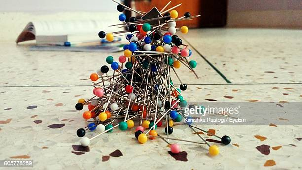 Close-Up Of Multi Colored Thumbtacks Stuck On Magnet At Floor