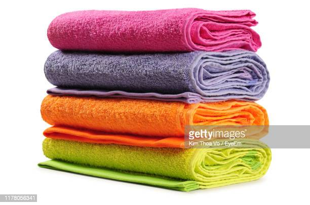 close-up of multi colored towels against white background - towel stock pictures, royalty-free photos & images