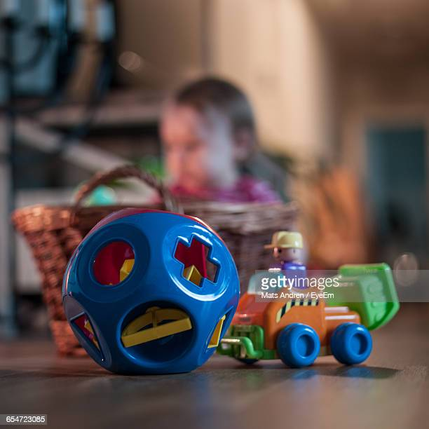 Close-Up Of Multi Colored Toys On Floor Against Baby In Wicker Basket
