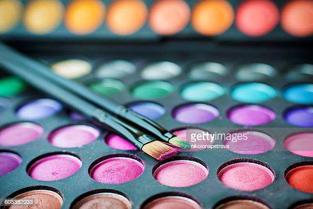 close-up of multi-colored eyeshadow palette and make up brushes - vanity stock pictures, royalty-free photos & images