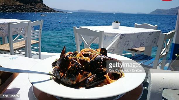 Close-Up Of Mussels Pasta Served In Plate On Restaurant Table By Amoudi Bay At Santorini Island