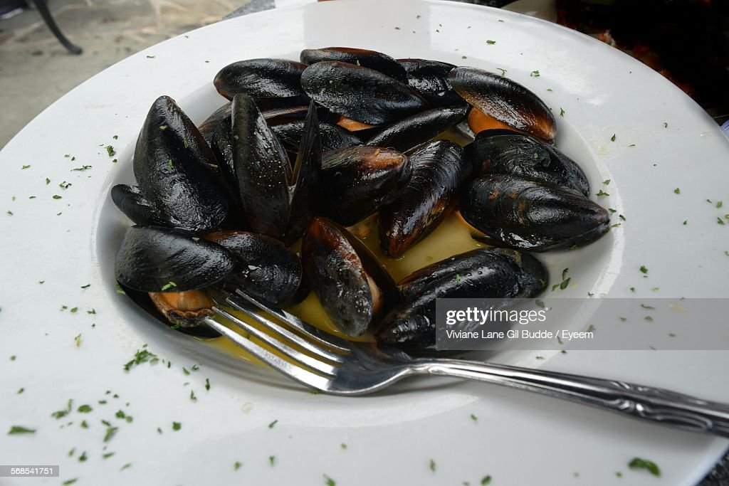 Close-Up Of Mussels With Fork Served In Plate : Stock Photo
