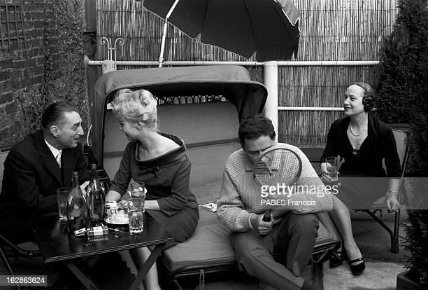 Close-Up Of Mylene Demongeot. Avril 1958. Mylène DEMONGEOT et son mari Henri COSTE une raquette à la main, prennent un verre à l'ombre d'un parasol,...