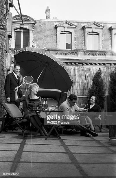 Close-Up Of Mylene Demongeot. Avril 1958. Mylène DEMONGEOT une raquette à la main, et son mari Henri COSTE prennent un verre à l'ombre d'un parasol,...