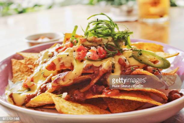 close-up of nachos in plate on table - ナチョス ストックフォトと画像