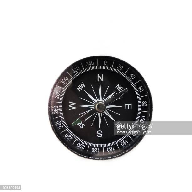 close-up of navigational compass against white background - compass stock pictures, royalty-free photos & images