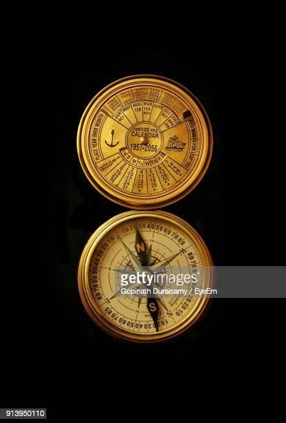 close-up of navigational compass on black background - compass stock pictures, royalty-free photos & images