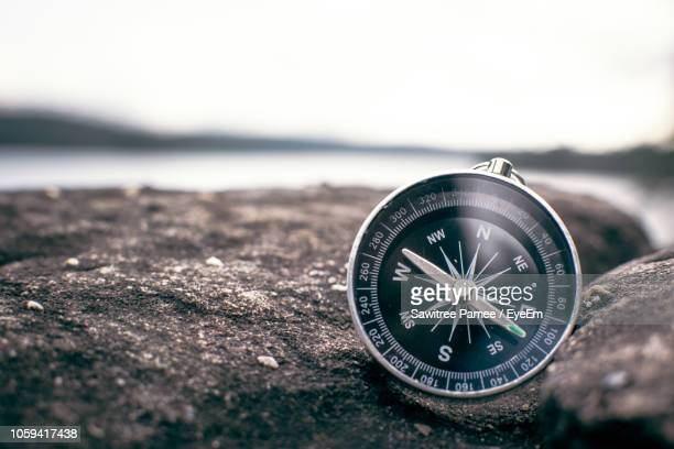 close-up of navigational compass on stone wall by lake - compass stock pictures, royalty-free photos & images