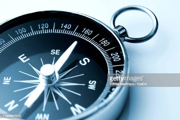 close-up of navigational compass on table - compass stock pictures, royalty-free photos & images