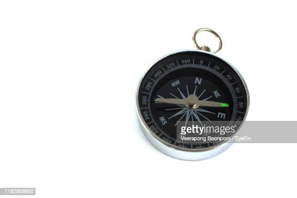 close-up of navigational compass on white background - compass stock pictures, royalty-free photos & images