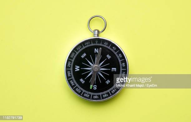 close-up of navigational compass on yellow background - compass stock pictures, royalty-free photos & images