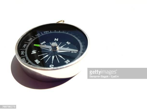close-up of navigational compass over white background - compass stock pictures, royalty-free photos & images