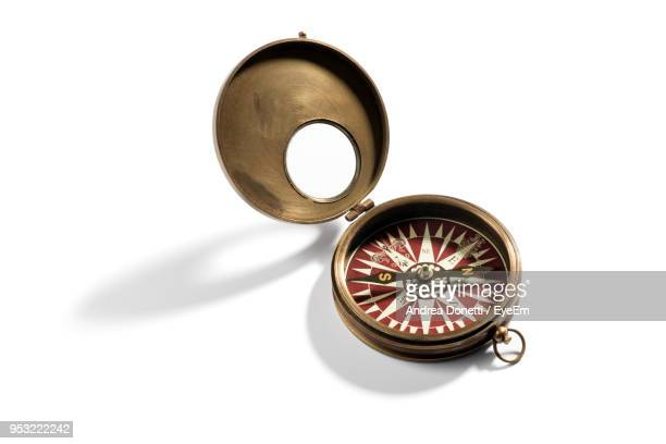 close-up of navigational compass over white background - compass stock photos and pictures