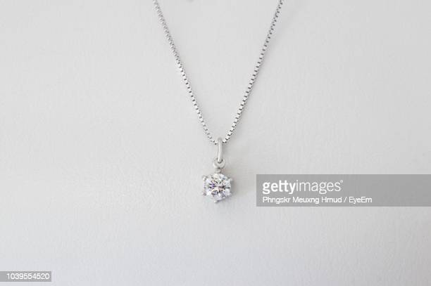 Close-Up Of Necklace Against White Background
