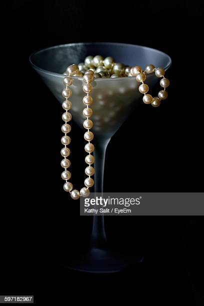 Close-Up Of Necklace On Martini Glass Against Black Background