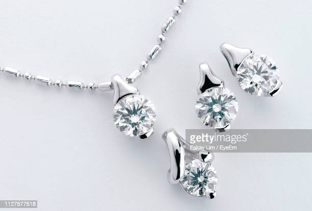 close-up of necklace with diamond pendants over white background - diamond necklace stock pictures, royalty-free photos & images