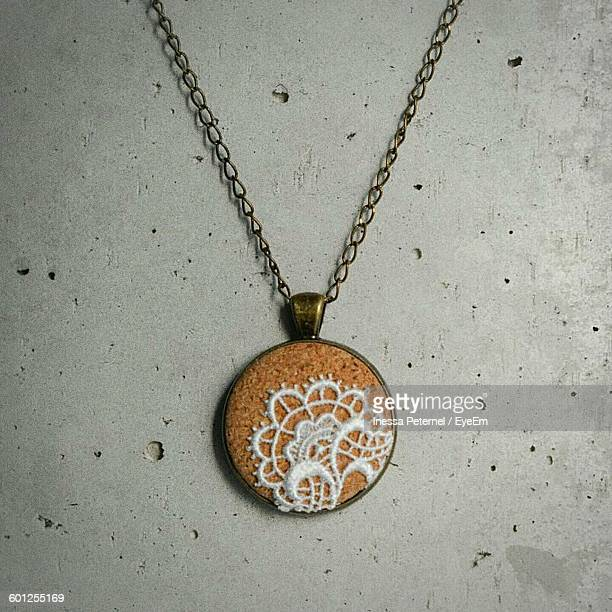Close-Up Of Necklace With Pendant On Wall