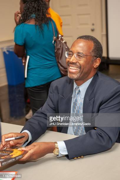 Close-up of neurosurgeon Ben Carson, smiling as he holds his book, during a Milton S Eisenhower Symposium at the Johns Hopkins University, Baltimore,...