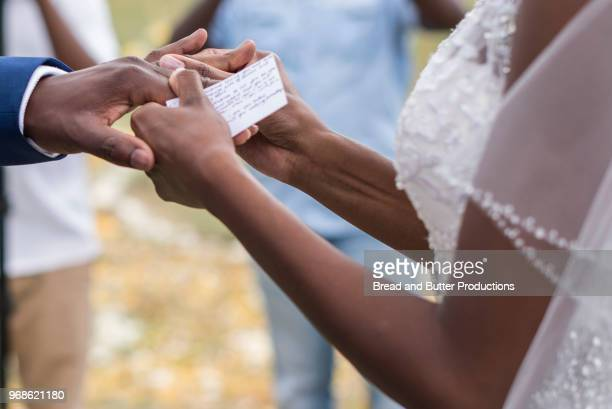close-up of newlywed couple exchanging rings at wedding ceremony - wedding vows stock pictures, royalty-free photos & images