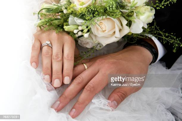 close-up of newlywed couple holding rose bouquet - wedding ring stock pictures, royalty-free photos & images