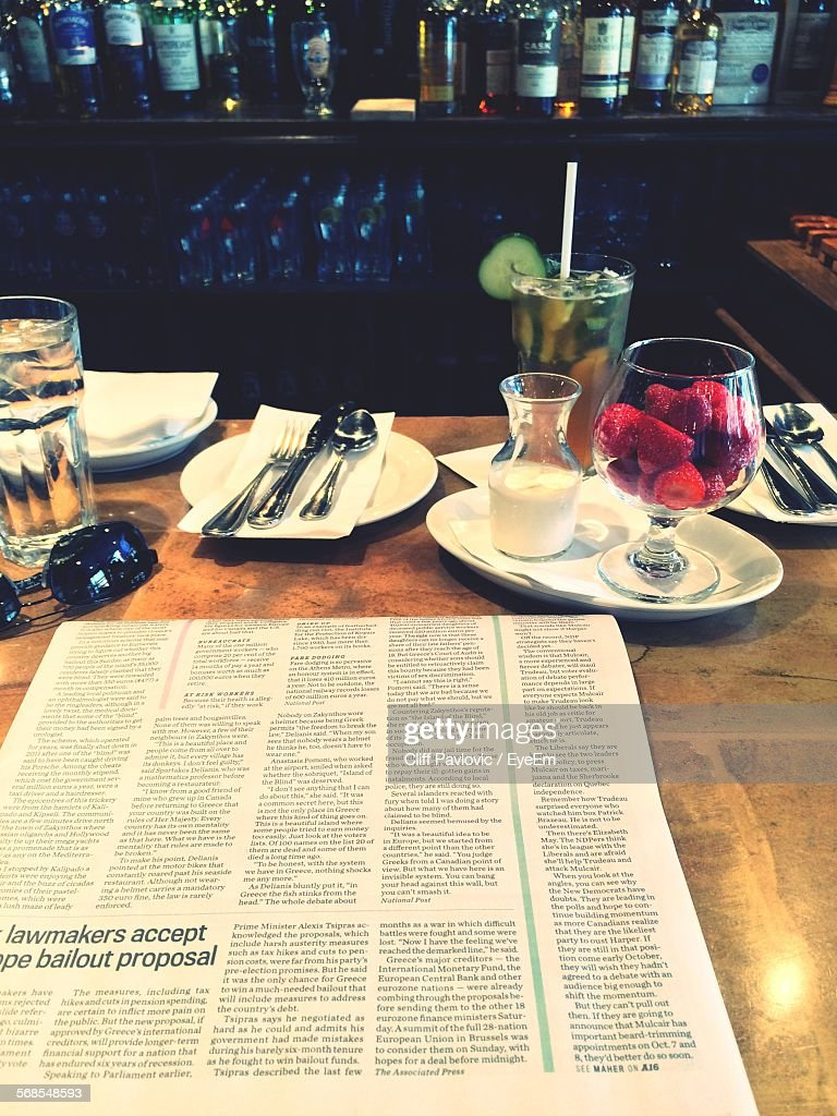Close-Up Of Newspaper On Table With Strawberries In Glass : Stock Photo