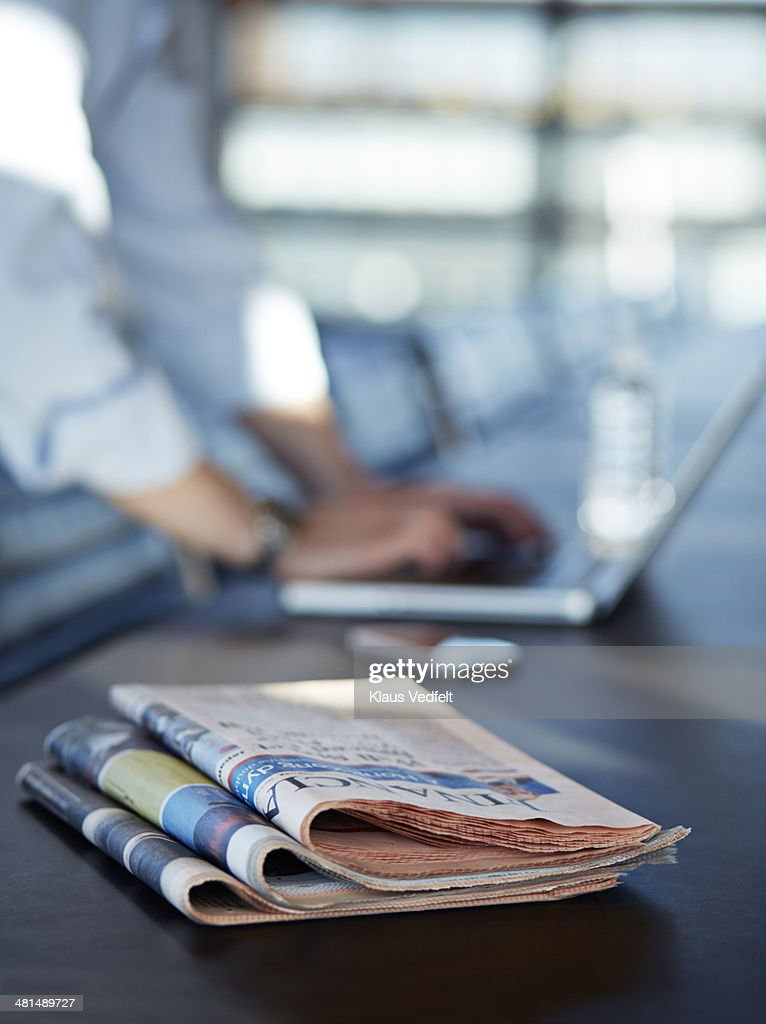 Close-up of newspapers & hands writing on laptop : Stock Photo