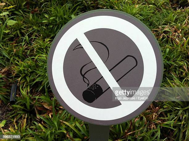 Close-Up Of No Smoking Sign Against Plants